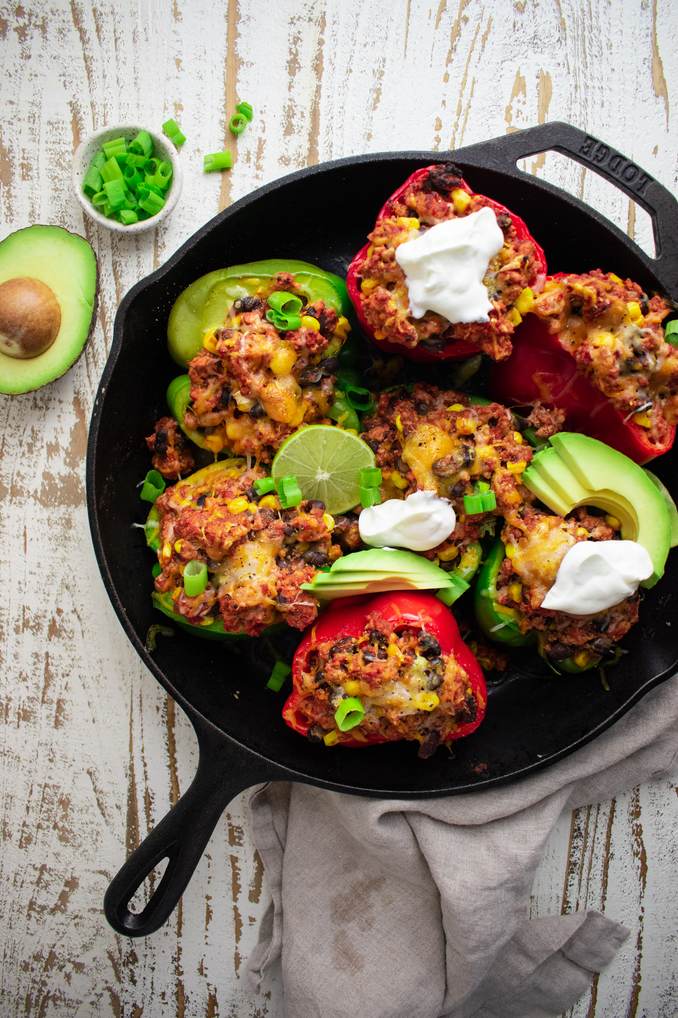birds eye view of stuffed peppers in a cast iron skillet topped with avocados scallions and limes