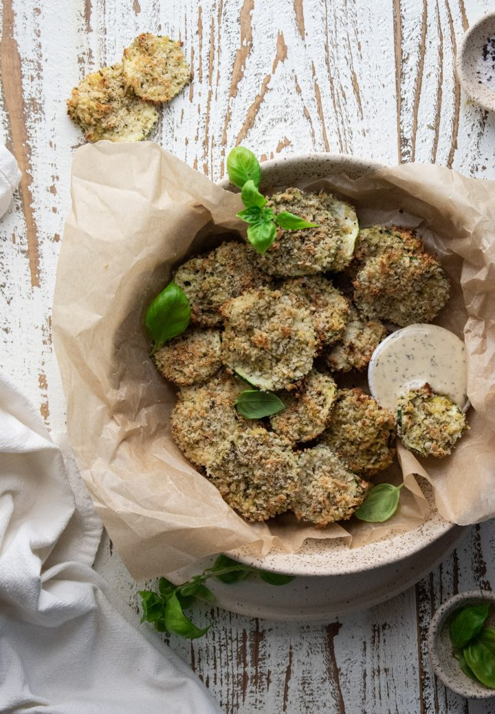 birds eye view of baked zucchini chips in a bowl lined with parchment paper on a wooden white board