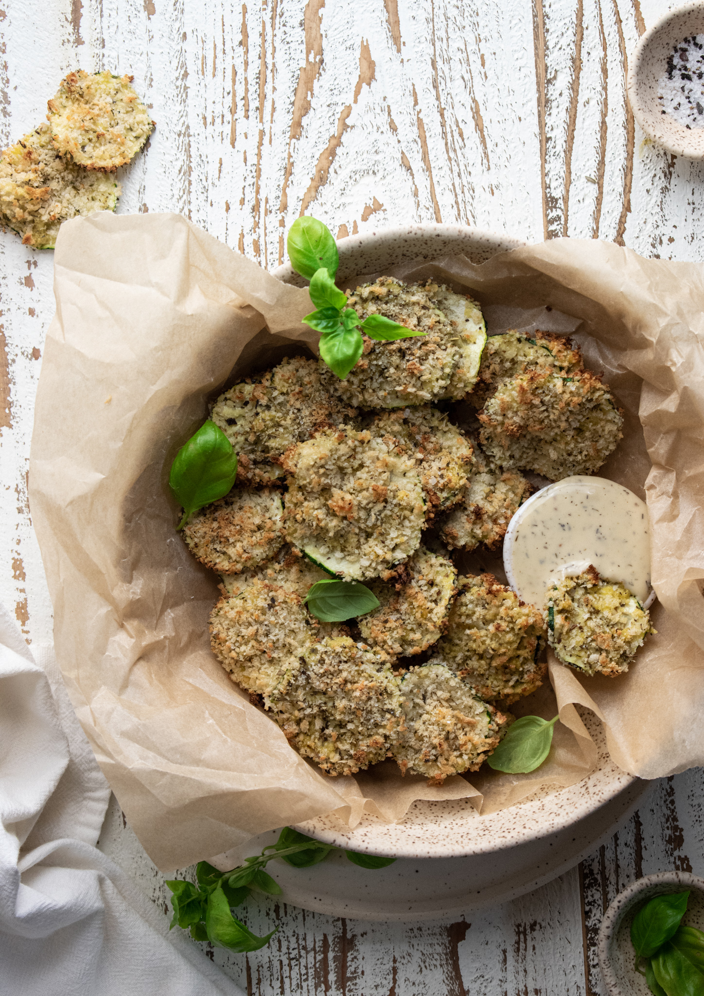 baked zucchini chips in a bowl filled with parchment paper on a wooden white board