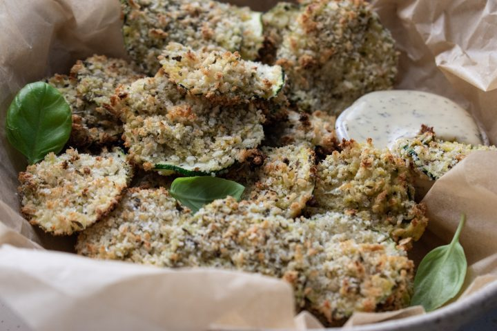 close up of oven baked zucchini chips in a bowl filled with parchment paper