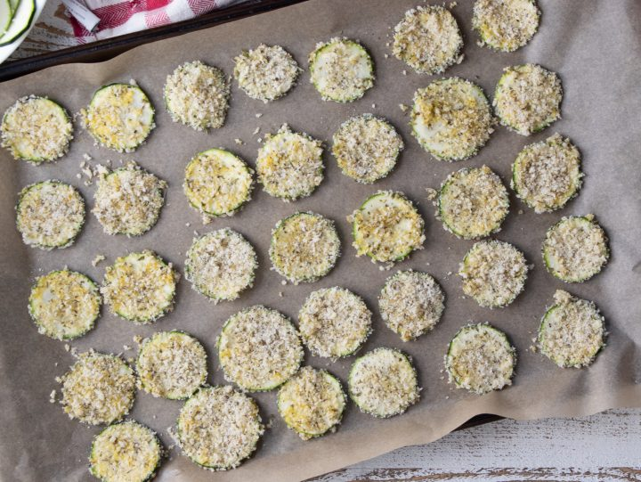 full tray of zucchini chips on a baking tray lined with parchment paper