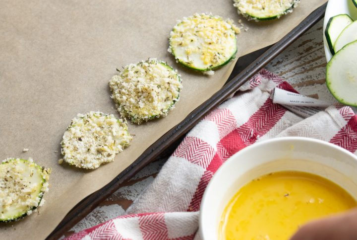 zucchini chips covered in panko breadcrumbs lined up on a baking tray