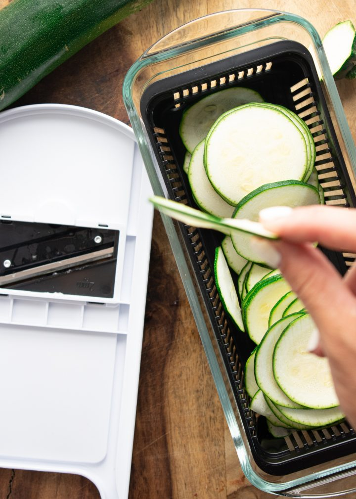 mandolin slicer and a hand holding very thin zucchini chips