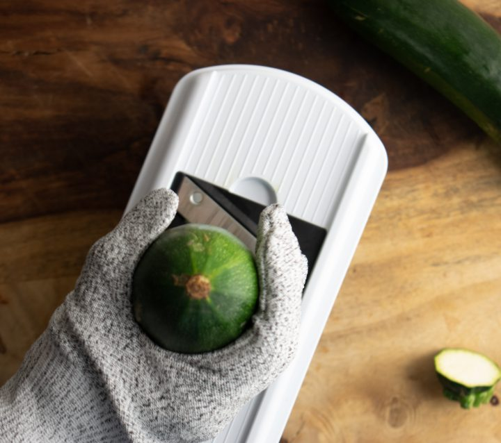 mandoline slicer with a hand wearing a safety glove and holding a zucchini to slice