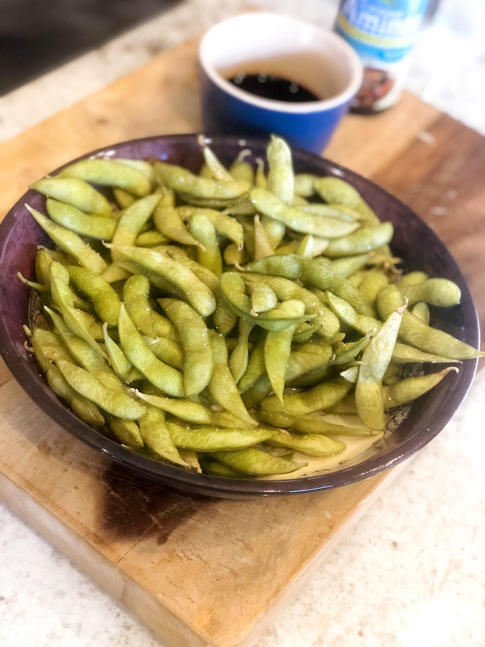 edamame in a purple bowl with a cup of coconut aminos