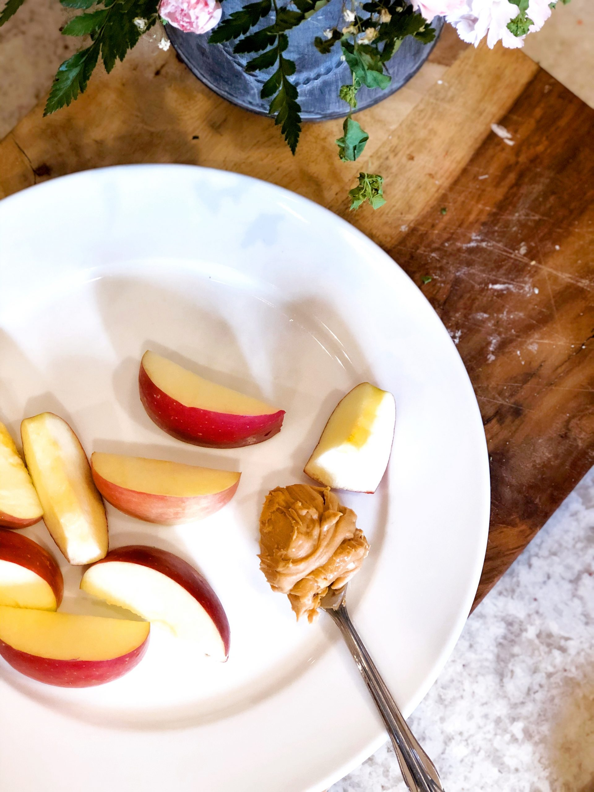 birds eye view of a chopped apple on a white plate with a spoonful of peanut butter