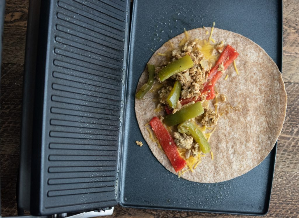 veggies and chicken added on top of cheese for making a healthy chicken quesadilla