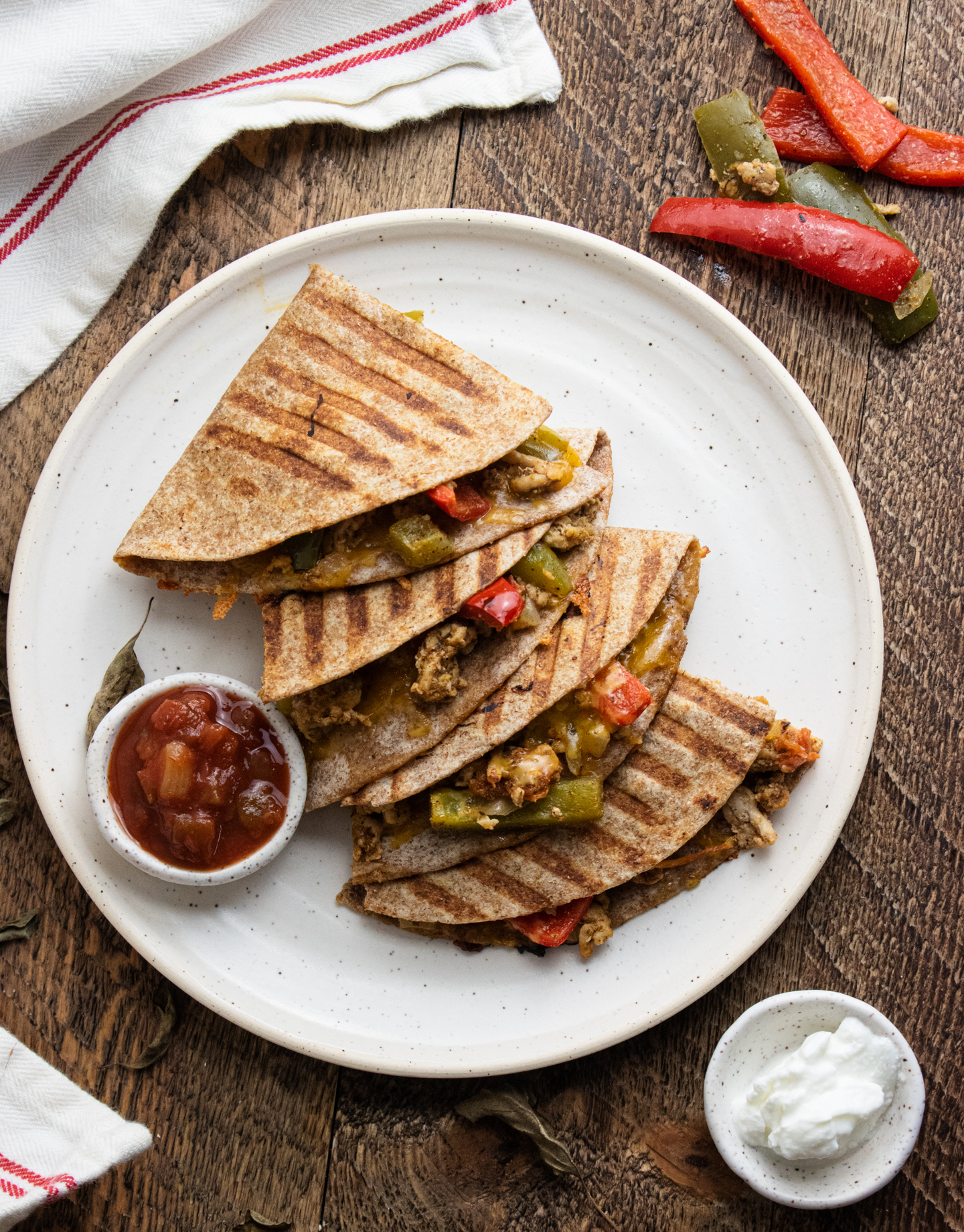 healthy chicken quesadillas on a white plate with salsa and plain greek yogurt for dipping