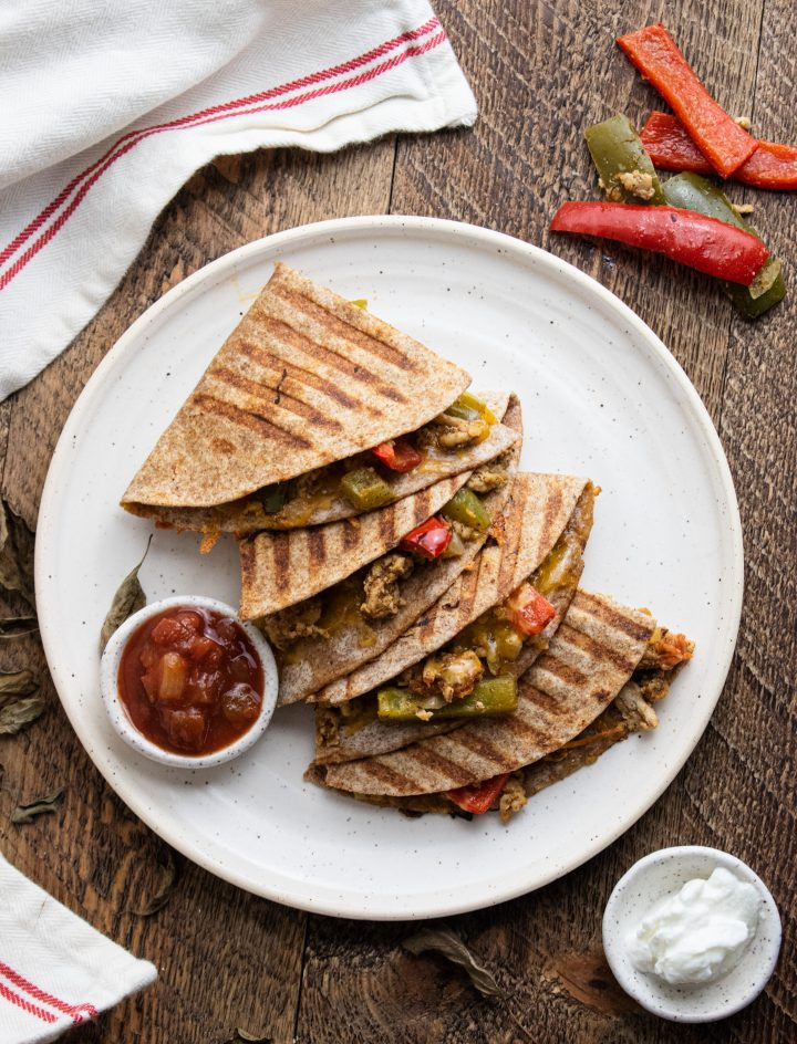 birds eye view of healthy chicken quesadillas on a white plate with salsa and plain greek yogurt for dipping