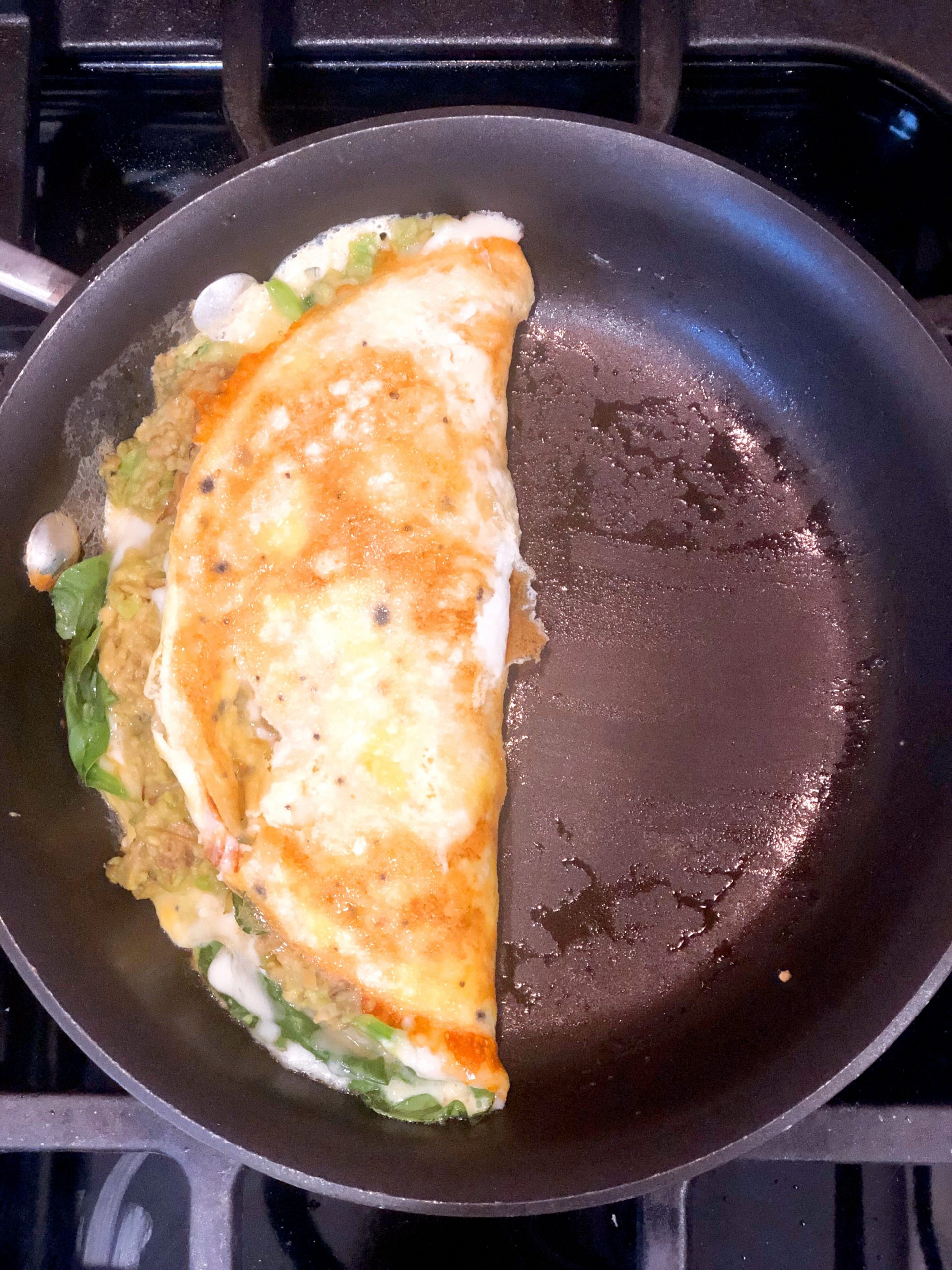 omelette folded over in a frying pan to create a half moon
