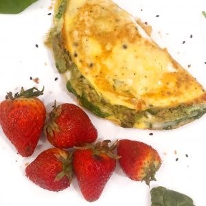 mashed avocado omelette on a white plate with strawberries