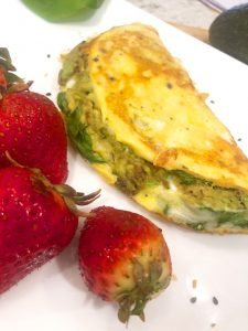 close up of mashed avocado omelette on a white plate with strawberries