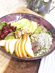 close up of a spinach salad with pears, avocado, bleu cheese, craisins, walnuts, and bosc pears