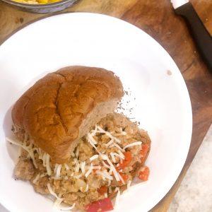 birds eye view of a healthy sloppy joe on a whole wheat bun on a white plate