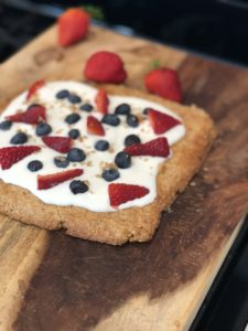 almond cookie tart with fruit on a wooden board with strawberries on the background