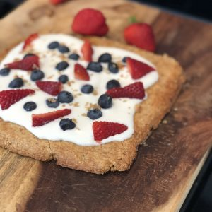 almond cookie tart with fruit on a wooden cutting board with strawberries in the background