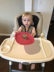 little blonde girl eating healthy cinnamon roll in her high chair