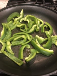 green bell peppers sauteeing in a pan