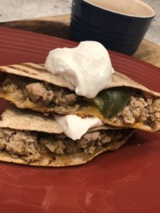 close up of ground turkey quesadillas on a red plate with plain greek yogurt on top