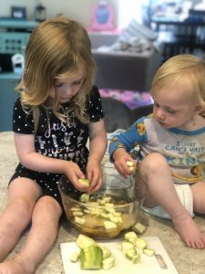 two little blonde children adding zucchini into a mixing bowl