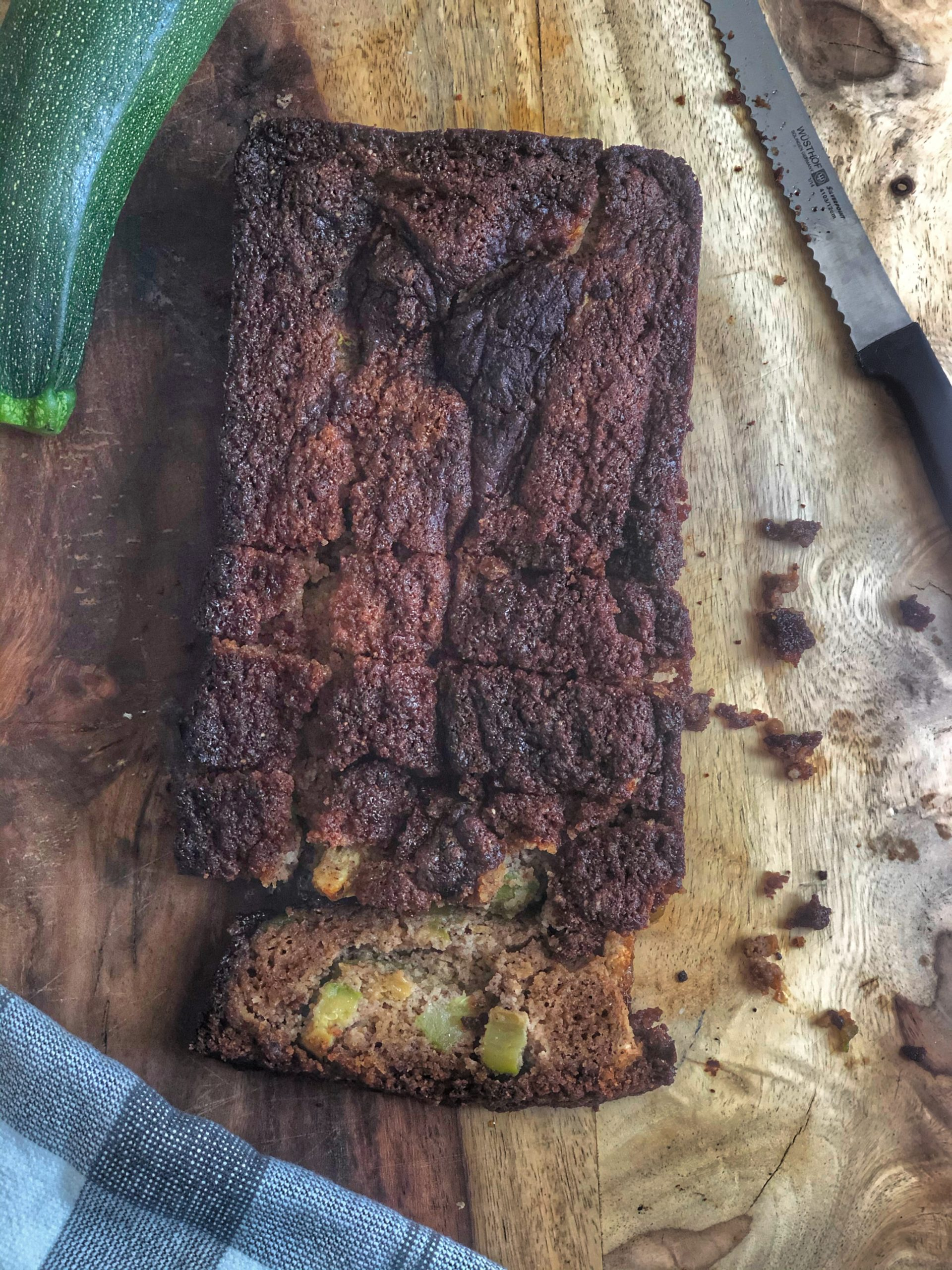 zucchini bread on a wooden board with a knife and a napkin