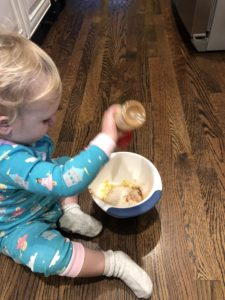 little blonde girl adding cinnamon to the whole wheat pancakes