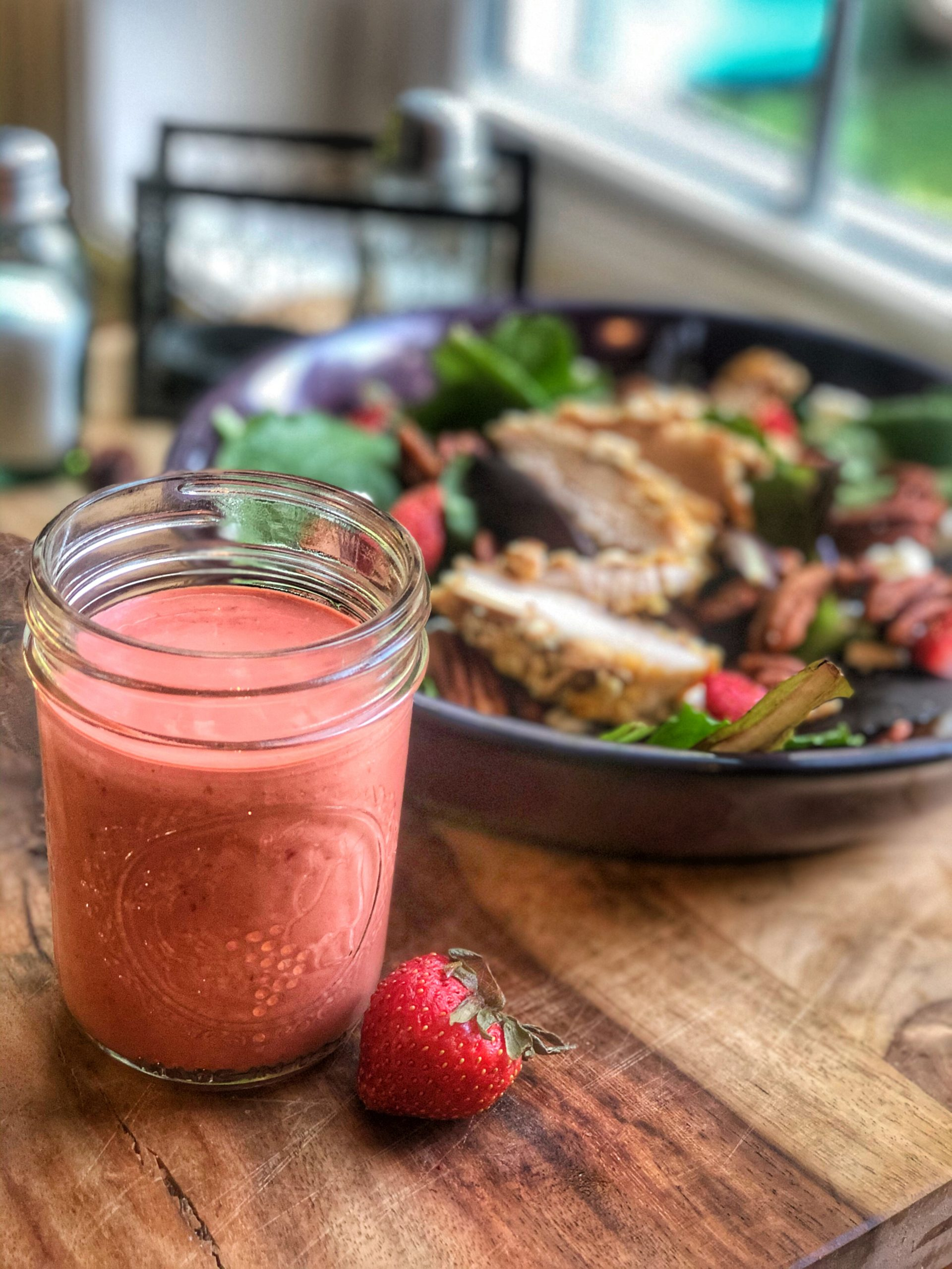 homemade strawberry vinaigrette dressing in a glass container with a salad in the background