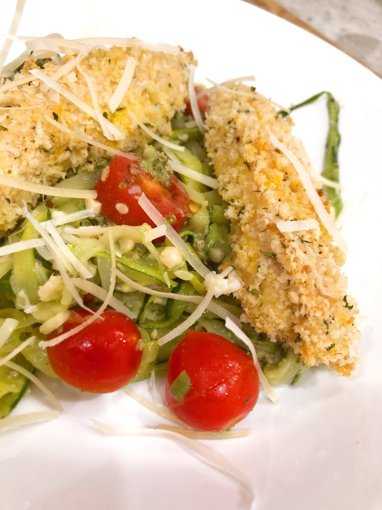 close up of panko chicken over zoodles with cherry tomatoes