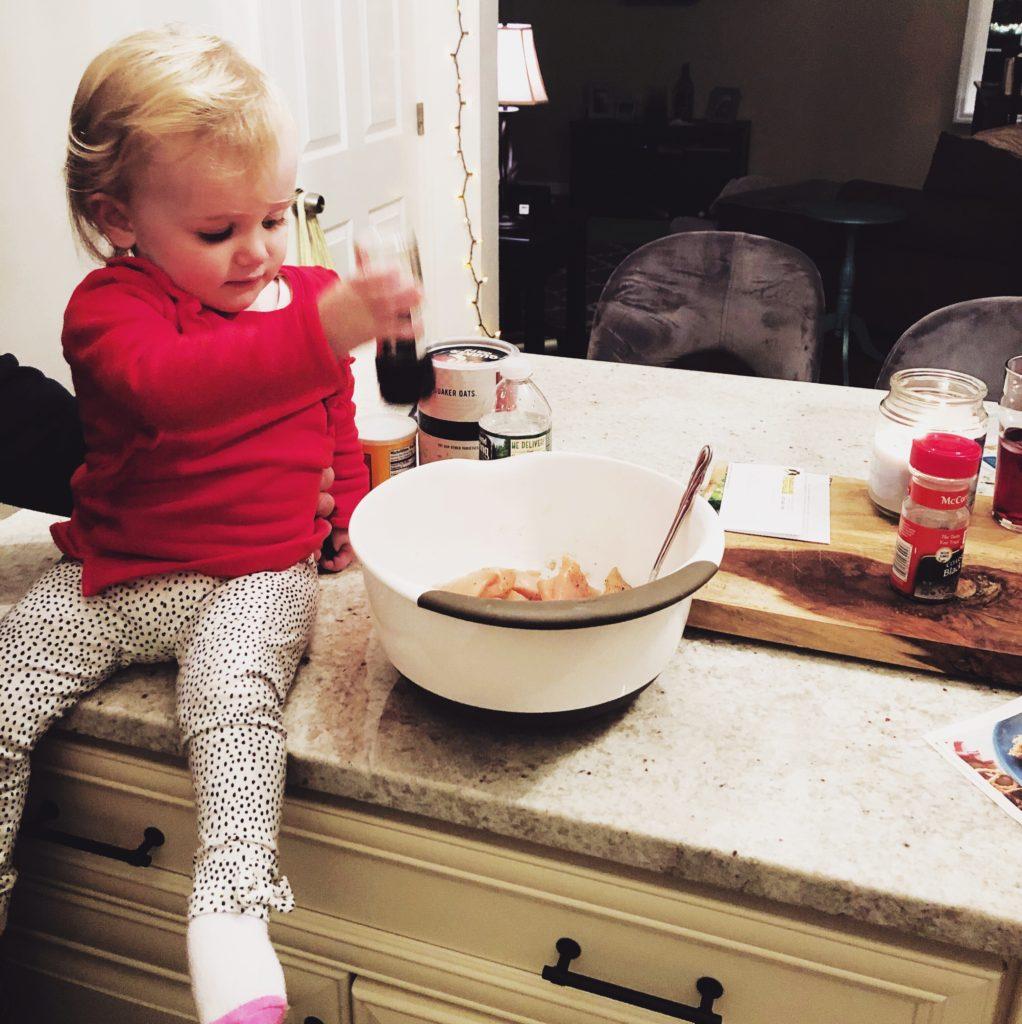 little blonde girl adding seasoning to the chicken