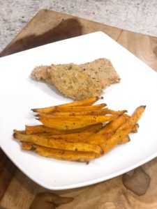 A pile of sweet potato french fries with some panko chicken.