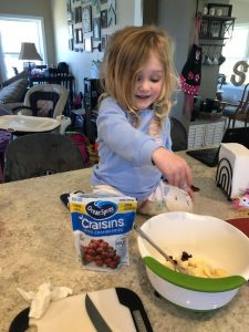little blonde girl adding dried craisins to the mixing bowl