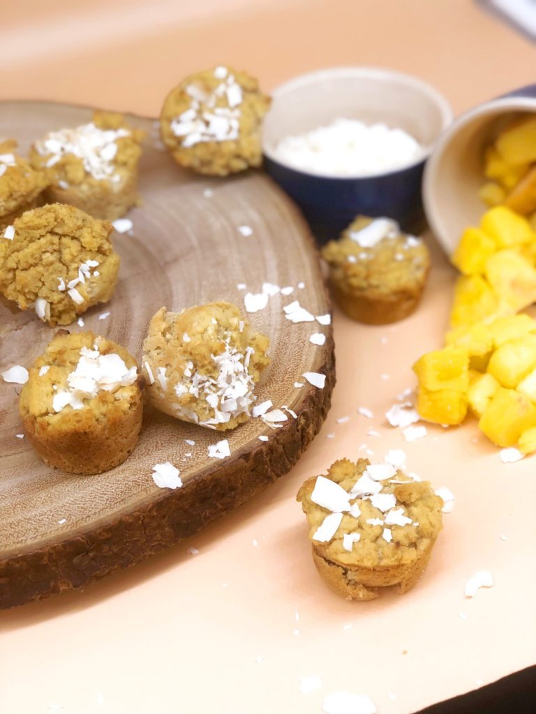 coconut mango mini muffins on a wooden board with coconut and mangos in the background
