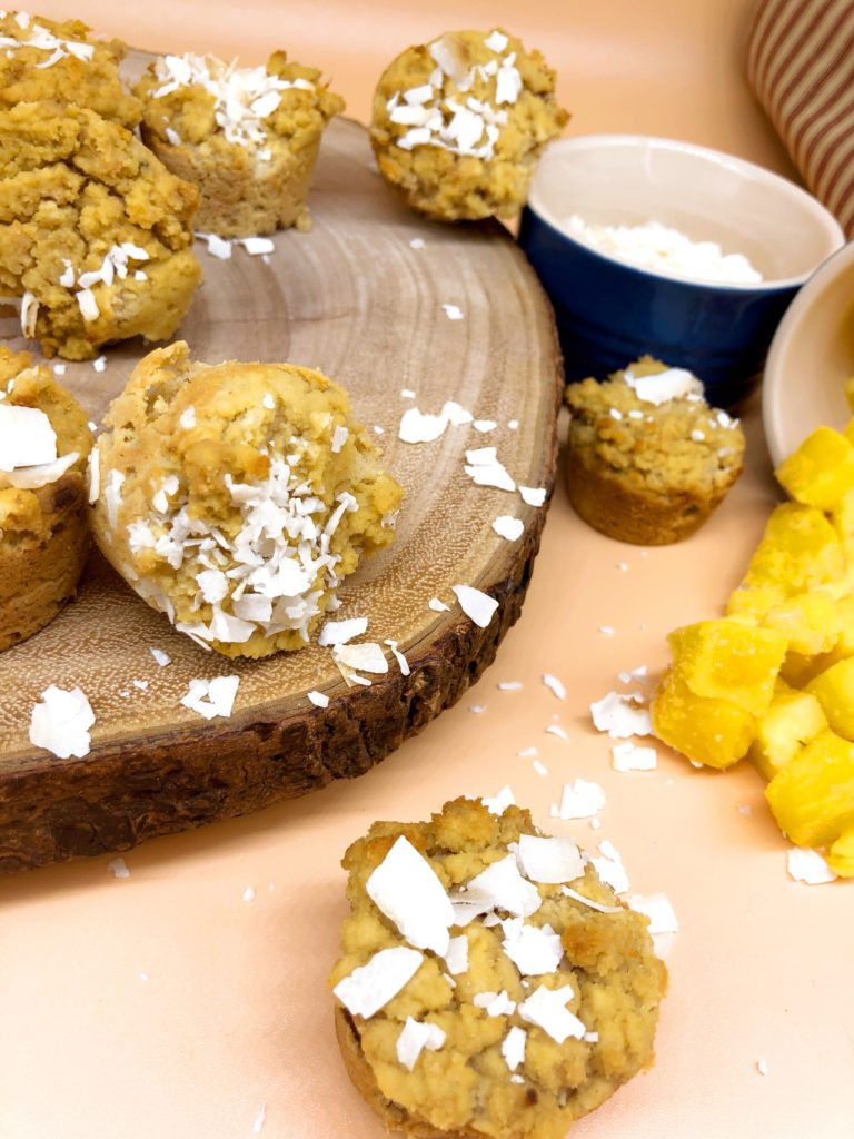 coconut mango mini muffins on a wooden board with coconut and mango in the background
