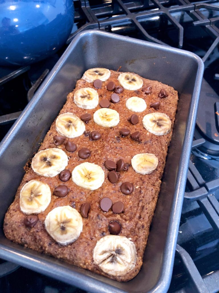 close up of flourless banana bread with chocolate chips and banana slices on top