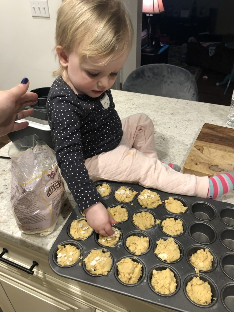 little girl putting coconut on the mango muffins