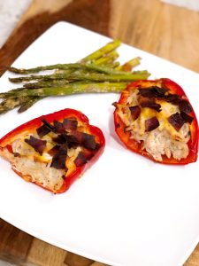 crack chicken in red bell peppers on a white plate with asparagus