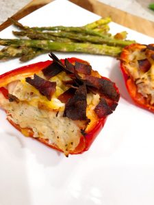 close up of crack chicken in red bell peppers on a white plate with asparagus