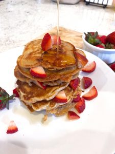 a strawberry pancakes stack being drizzles with pure maple syrup on a white plate