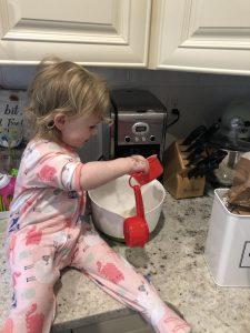 little blonde girl adding whole wheat flour to a big white bowl to make pancakes