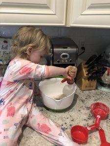 little blonde girl adding cinnamon to the pancake batter