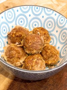 close up of super moist ground turkey meatballs in a decorative blue bowl