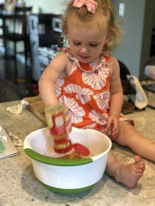 little blonde girl adding seasonings to a large white mixing bowl