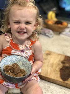 little blonde girl smiling with ground turkey meatlballs