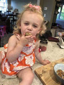 little blonde girl eating ground turkey meatballs