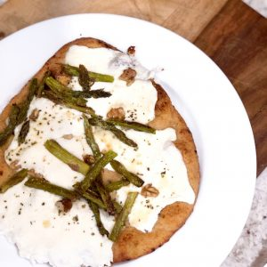 asparagus and naan pizza on a white plate on a wooden cutting board