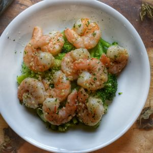 shrimp with parsley garlic butter in a white bowl over broccoli on a wooden cutting board