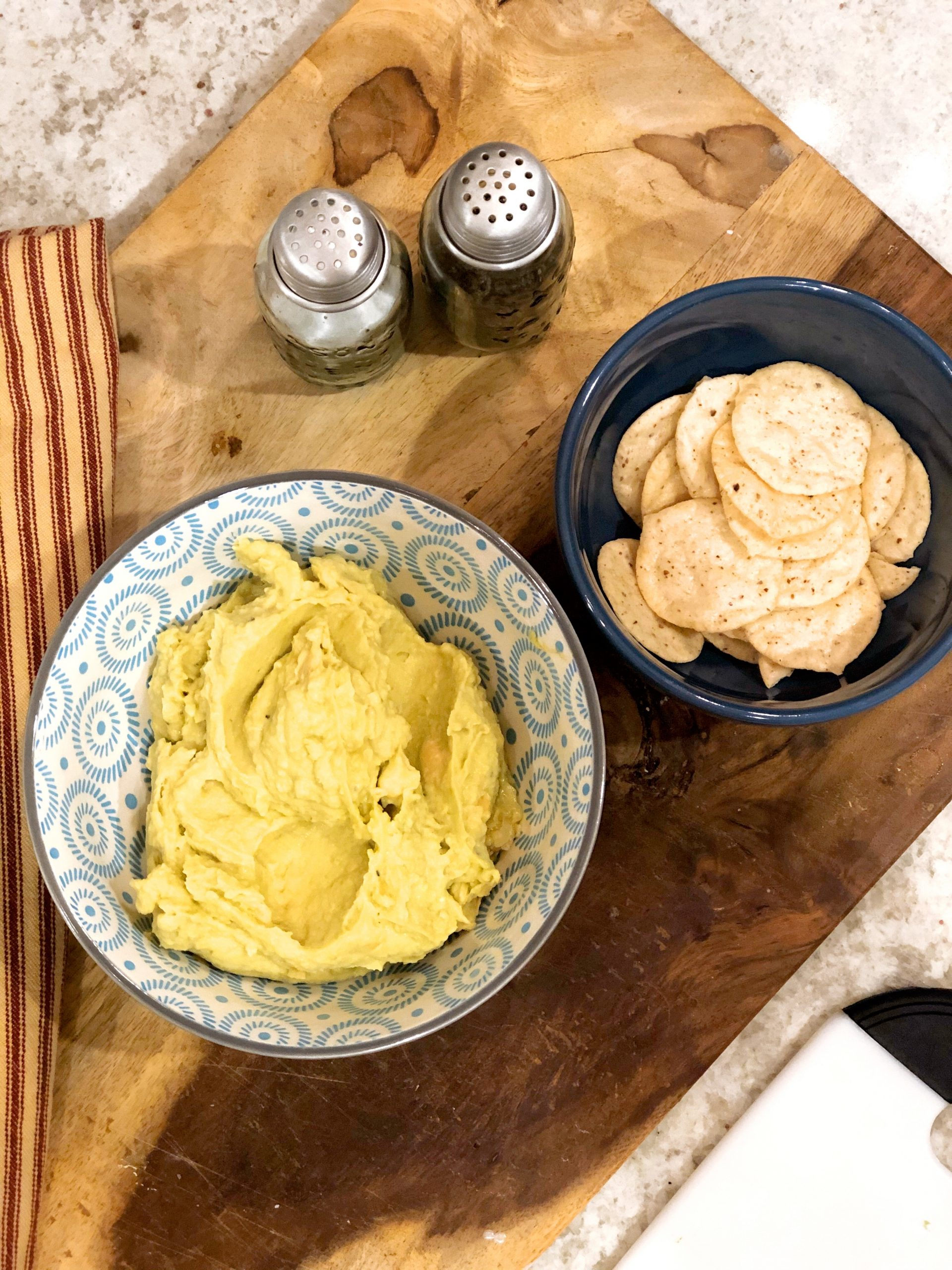 avocado hummus is a blue bowl with nut thins on the side