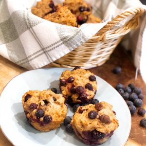healthy blueberry muffins in a basket and a few on a blue plate with some extra blueberries thrown on the side