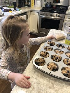 little girl sprinkling light brown sugar on top of the healthy blueberry muffins