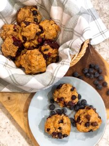 blueberry muffins in a basket and a few sitting on a blue plate
